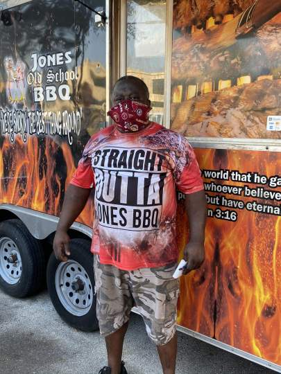 Mr. Jones standing in front of the food truck wearing a mask